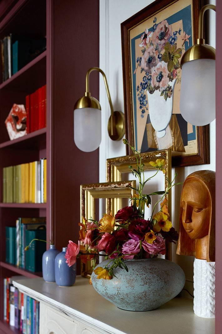 Каминный портал в квартире с картинами, рамками, старинными вазами