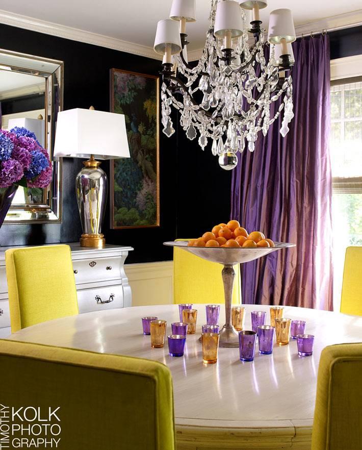 черные стены, фиолетовые шторы и желтые стулья в интерьере столовой комнаты