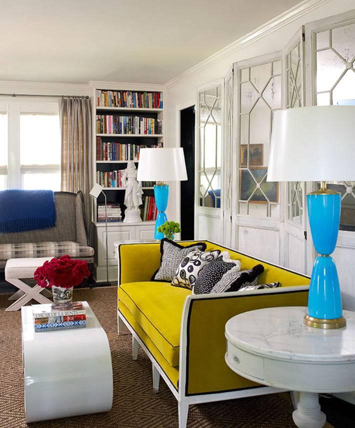 желтый диван и голубые настольные лампы в интерьере гостиной