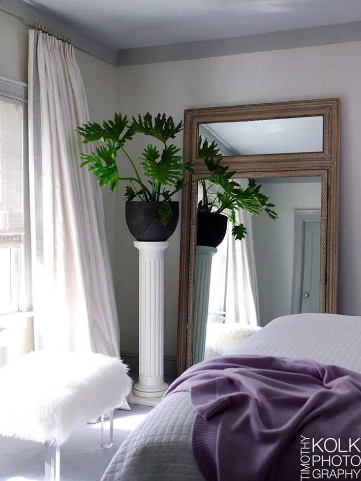 белый текстиль в спальне с большим зеленым комнатным растением