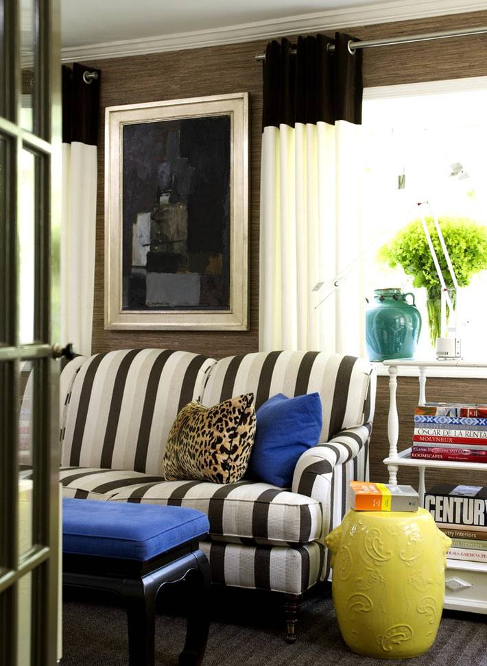яркие аксессуары в комнате с темными обоями и полосатым диваном фото