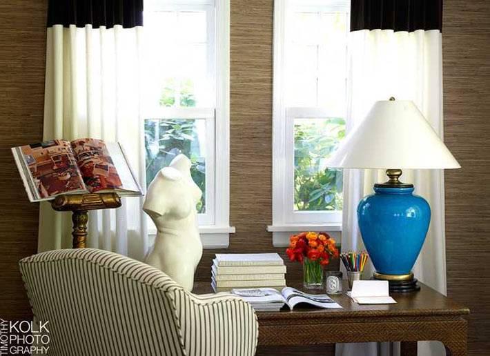 гипсовый бюст и синяя лампа на деревянном рабочем столе
