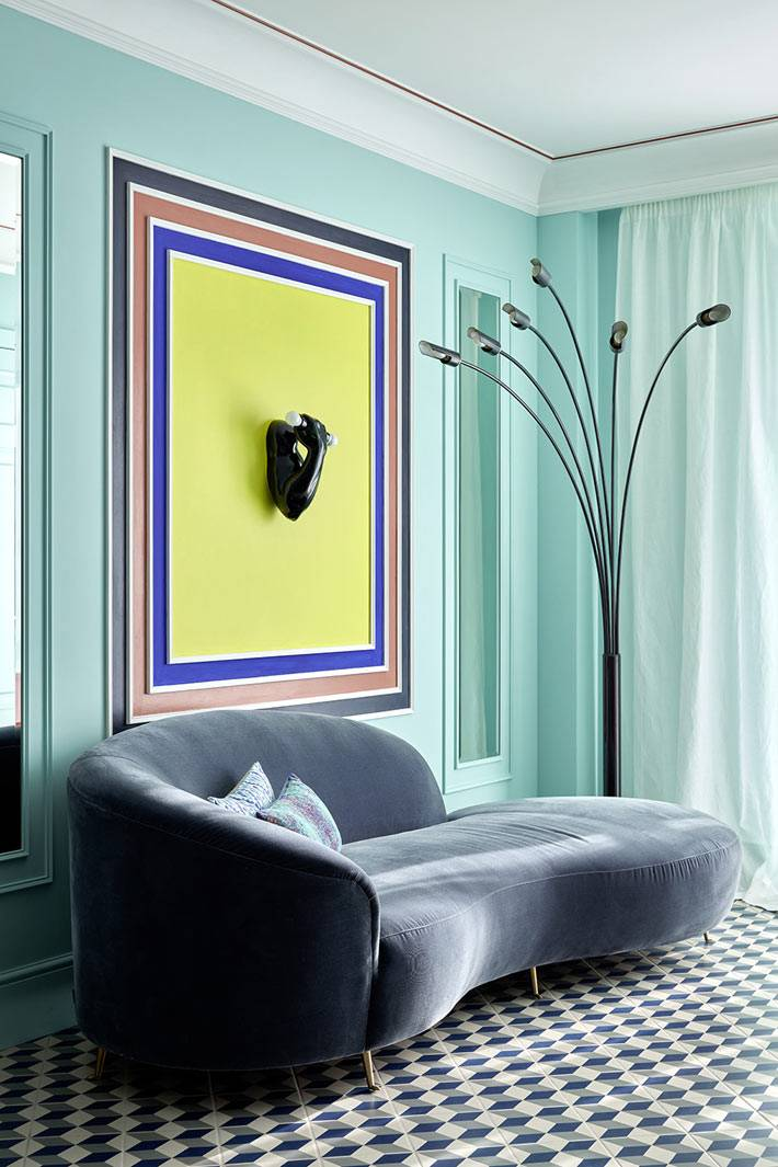 Бирюзовый цвет стен и уникальный диван в гостиной комнате квартиры
