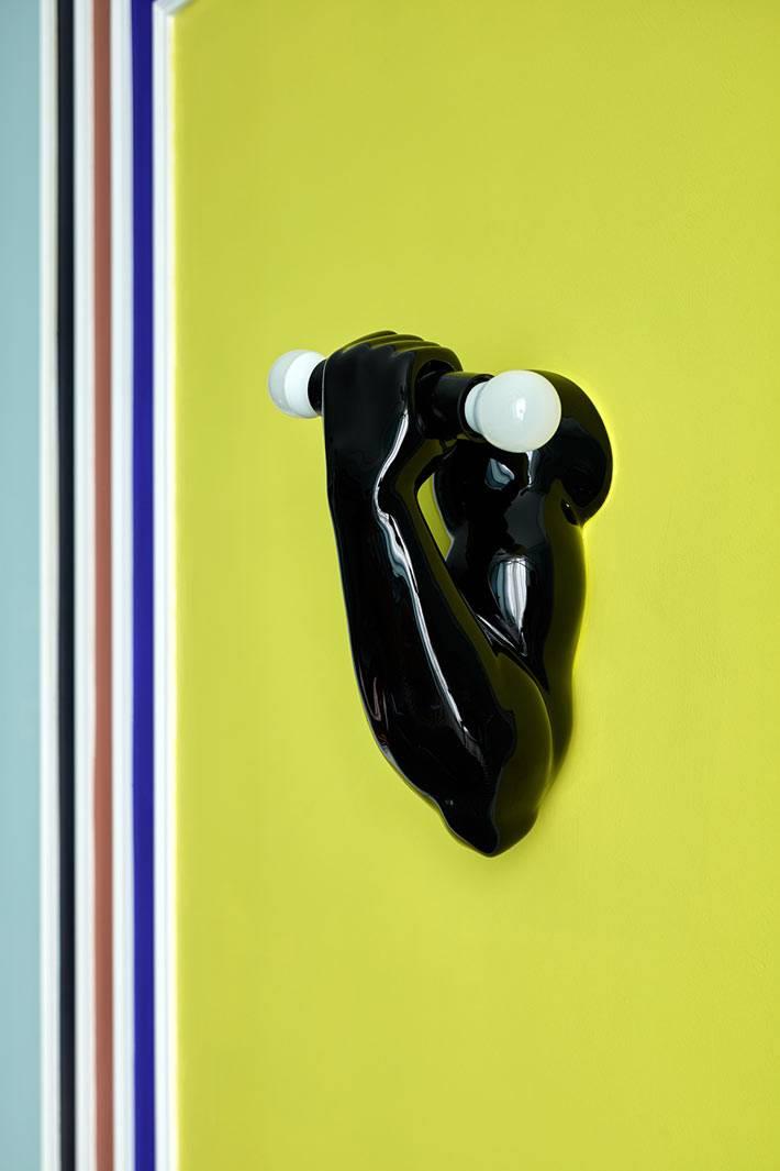 необычный светильник с черной рукой и гантелей фото