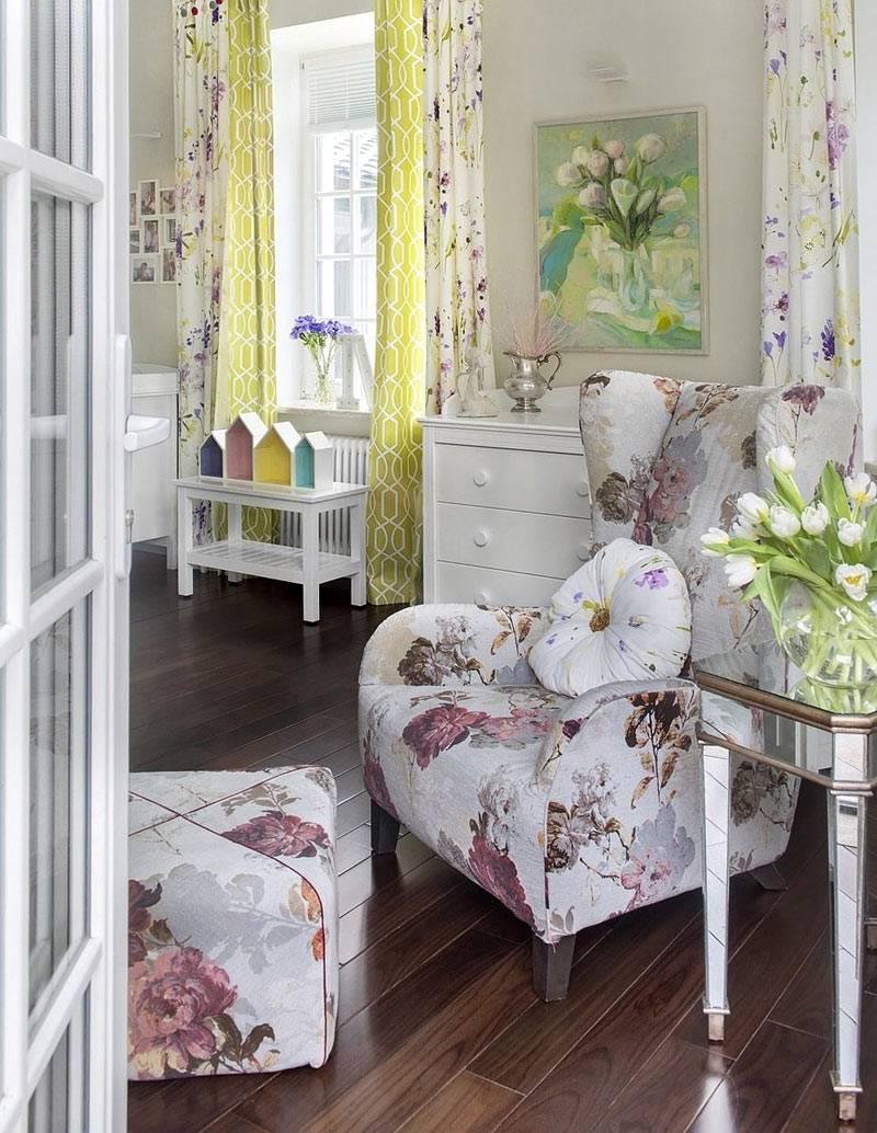 удобное кресло с пуфом с цветочным принтом в интерьере детской