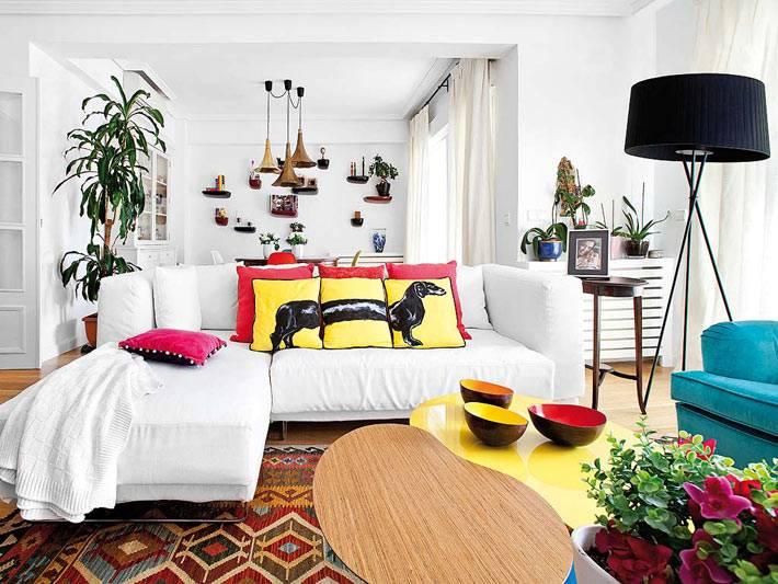 яркие диванные подушки на белом диване в гостиной комнате