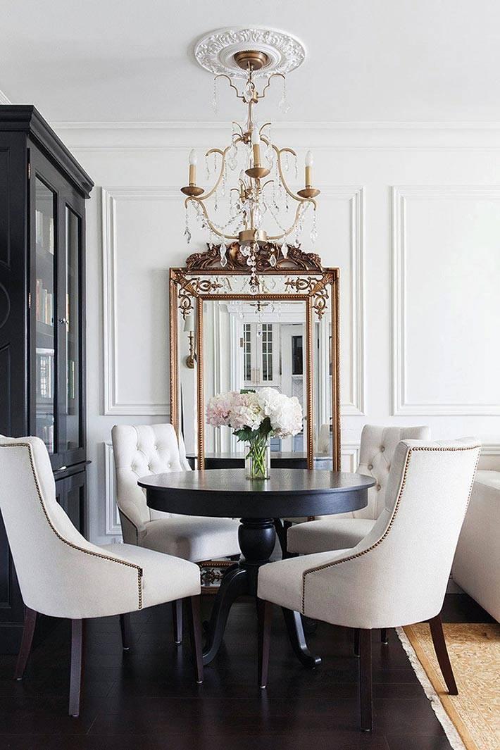 черный обеденный стол и белые мягкие стулья в гостиной