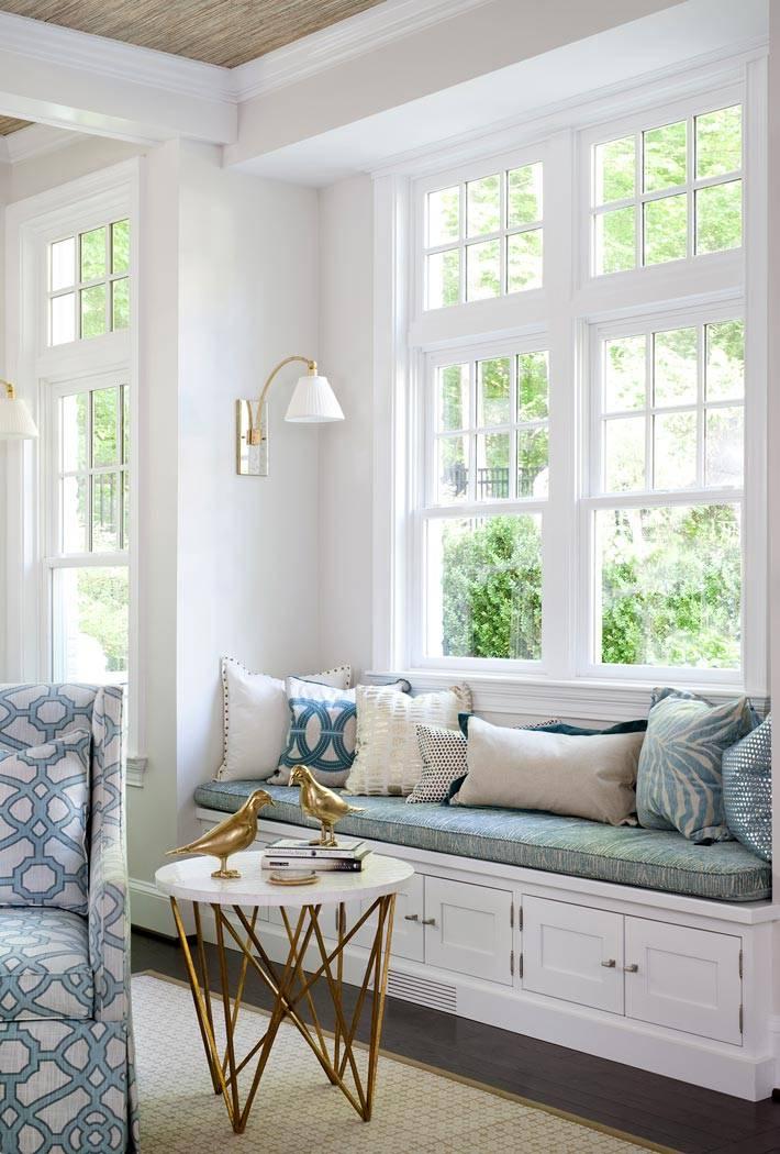 мягкая подоконная скамья с подушками у окна