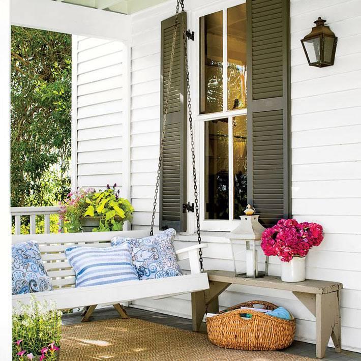 белая подвесная лавка-качеля на веранде дома фото