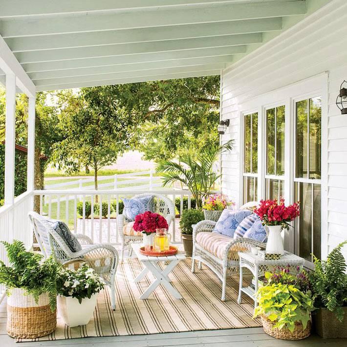 Белая плетеная мебель на белой веранде дома фото
