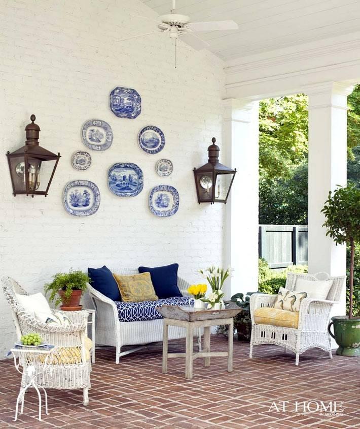 синие декоративные тарелки на булой стене веранды офто