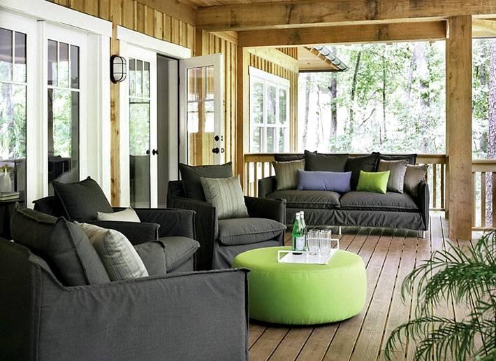 черные мягкие диваны и кресла на деревянной веранде