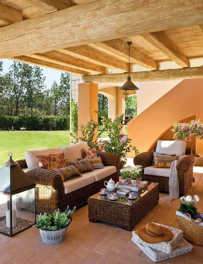 плетеная мебель и различные аксессуары на веранде у дома