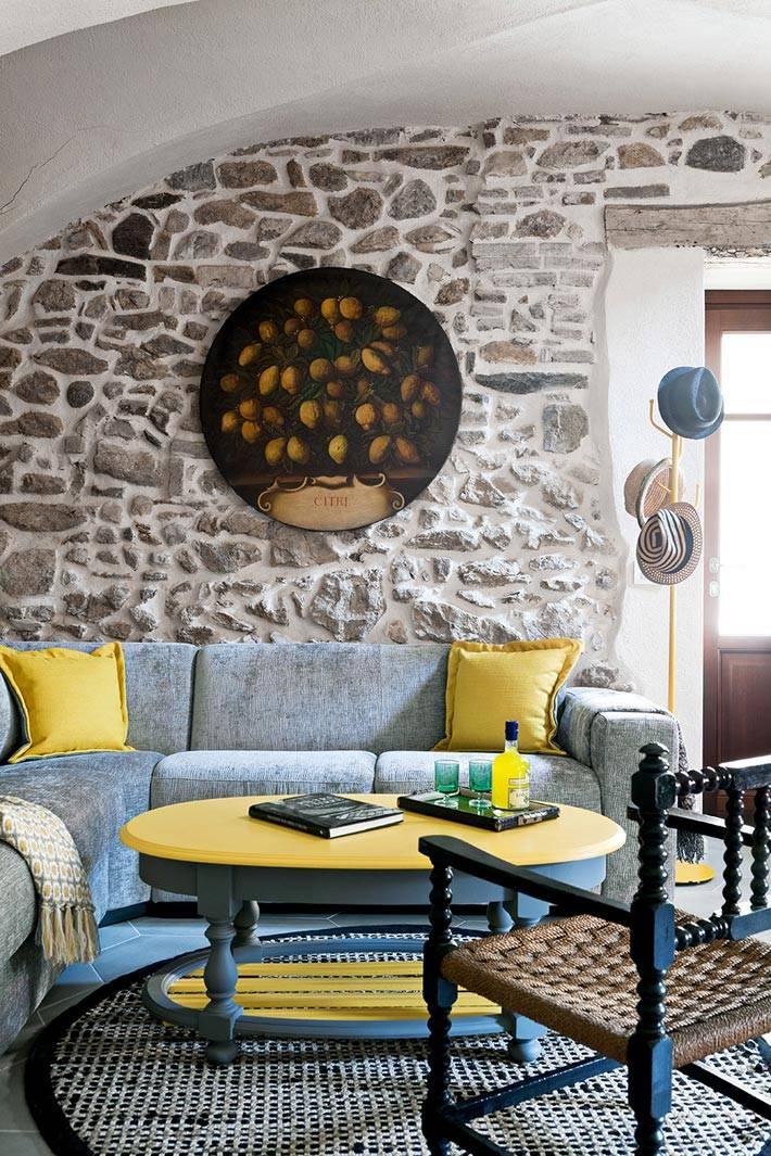 сочетание серого и желтого цвета в гостиной с каменными стенами фото
