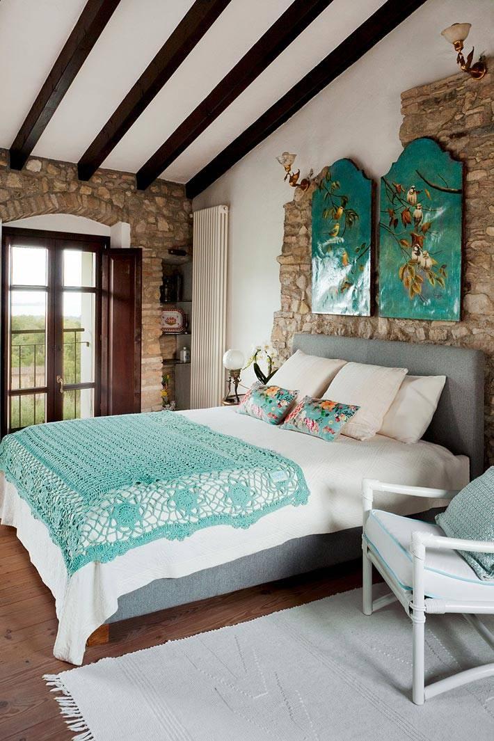 мансардная спальня с бирюзовыми оттенками на картине и кровати