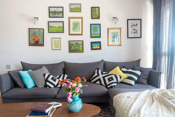 картины с пейзажами и натюрмортами на стене в гостиной комнате