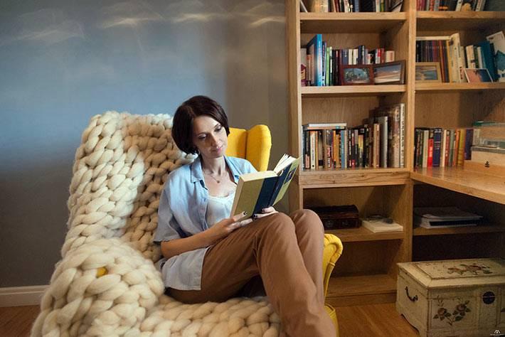комфортное кресло и плед для чтения в комнате с книгами