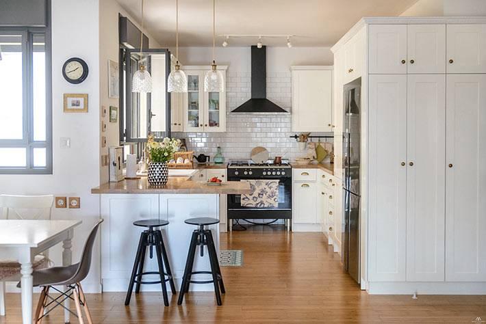 Белый дизайн кухни с барной стойкой и множеством шкафчиков