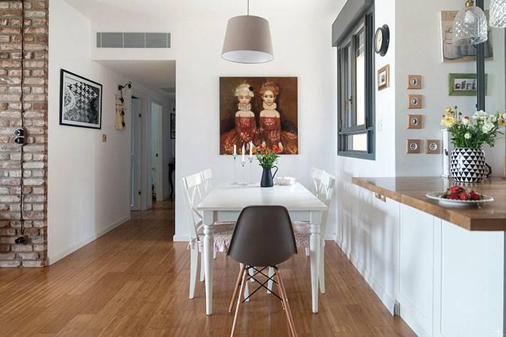 большой белый обеденный стол возле красивой картины