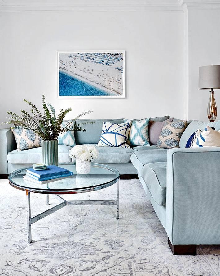 Голубой угловой диван и серый ковер в гостиной комнате фото