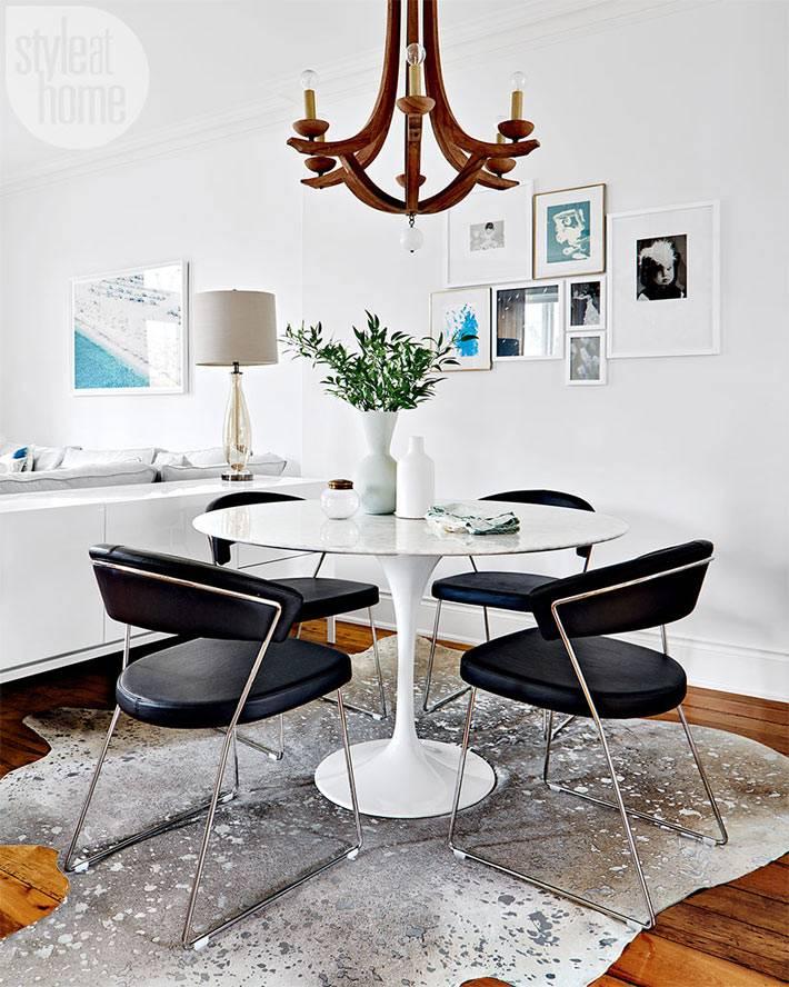 Круглый белый обеденный стол с мягкими черными стульями в столовой