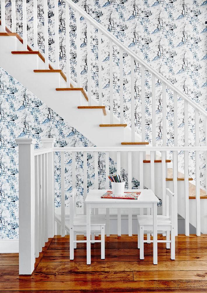 белая лестница на фоне пестрых обоев с флористическим узором
