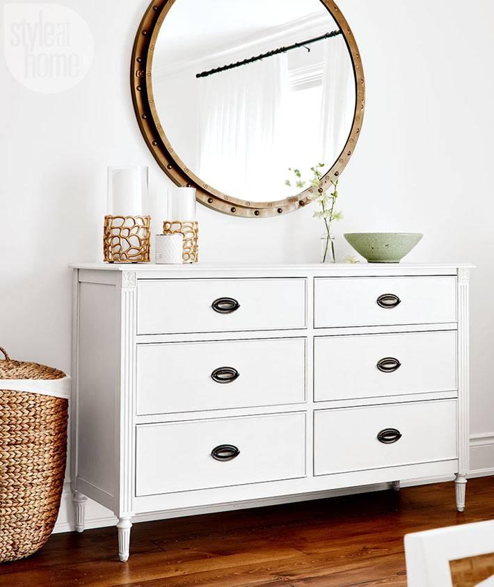 Большой белый комод и круглое зеркало в спальне фото
