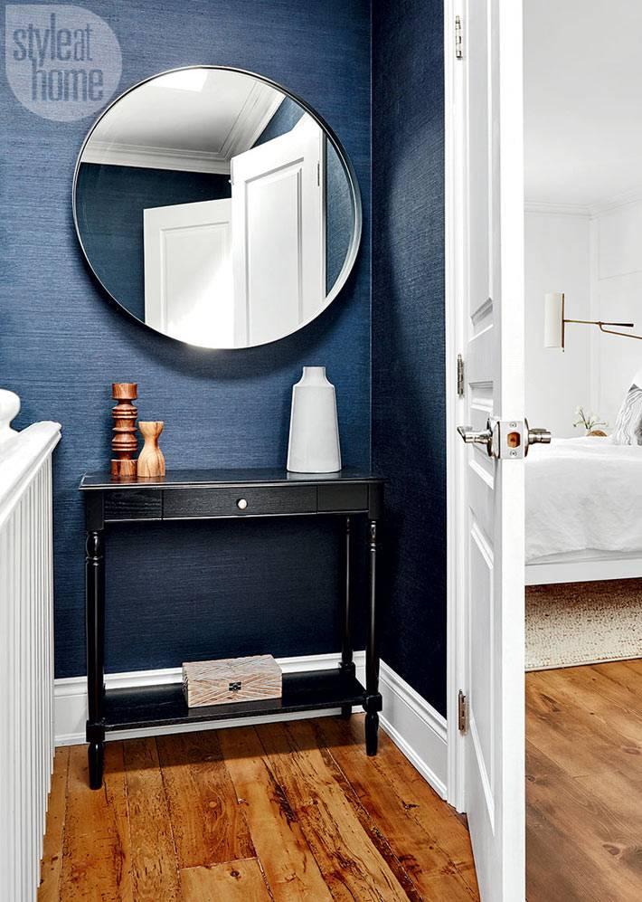 темно-синяя стена в доме, большое круглое зеркало и черная консоль фото
