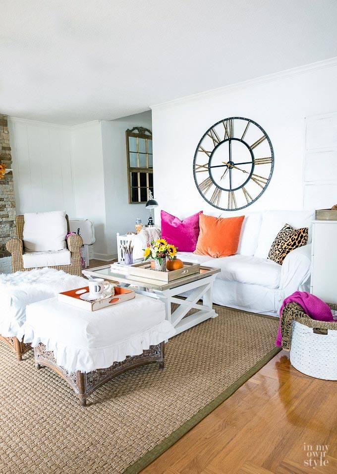 белая гостиной комната с яркими подушками на диване