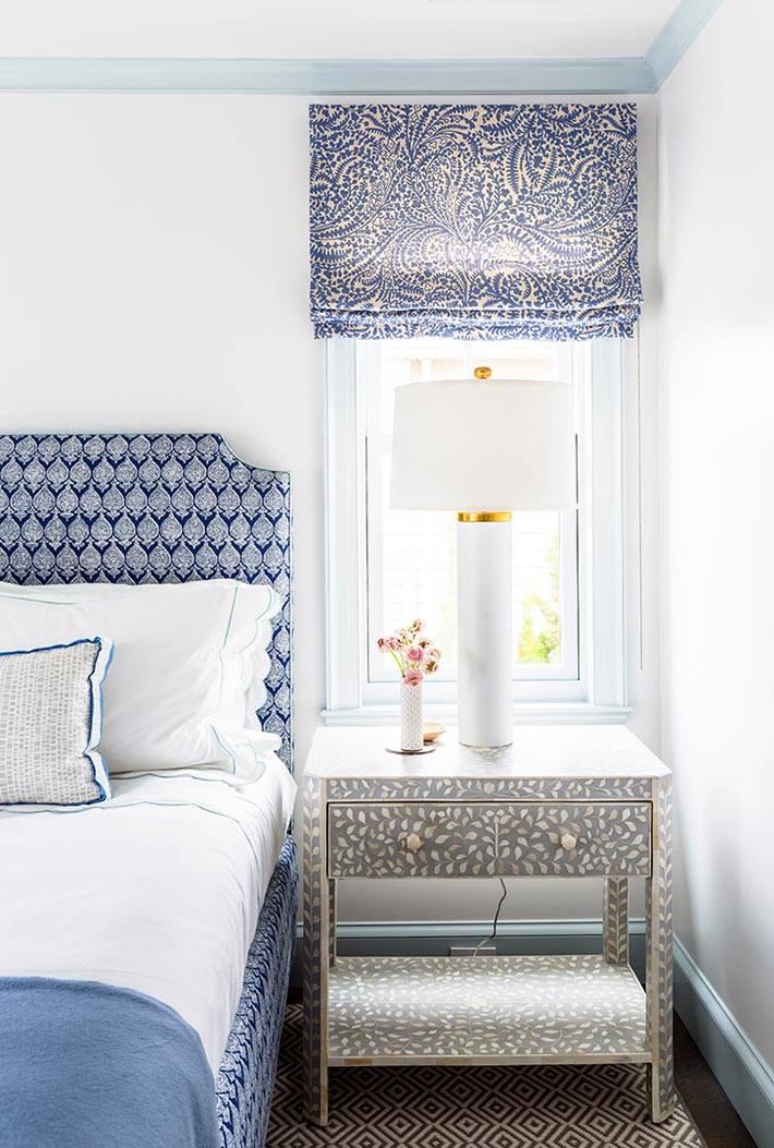 на серой прикроватной тумбе стоит белый светильник в спальне