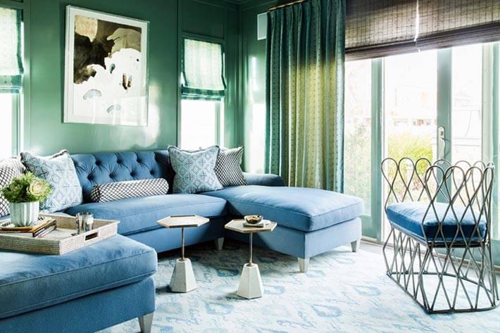 интерьер комнаты с зелеными стенами и синим диваном