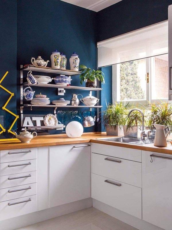 синие стены на кухне, открытые полки для посуды и окно перед раковиной