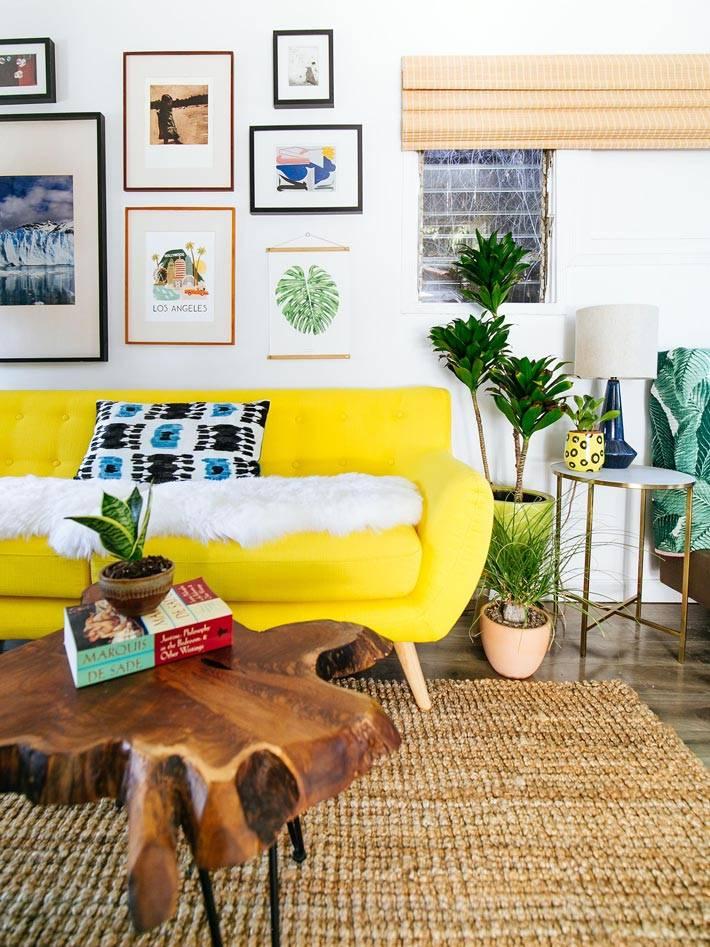 яркий желтый диван и столик из среза дерева в гостиной