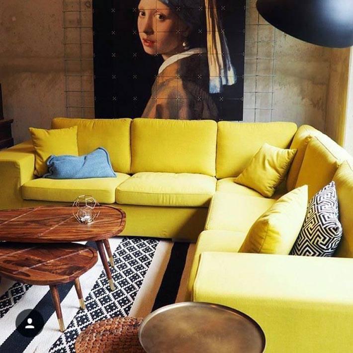 угловой диван желтого цвета в темной комнате