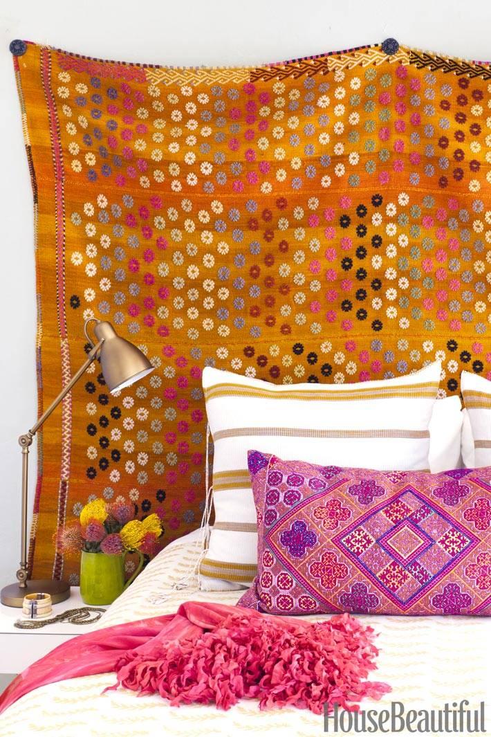 Оранжевый гобелен в изголовье кровати добавляет красок спальне
