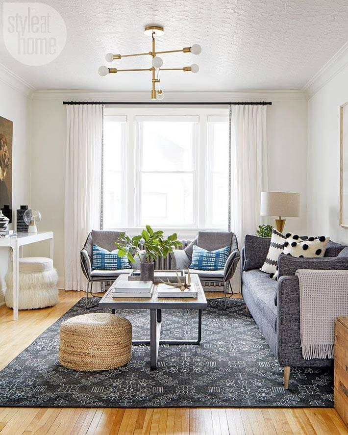 гостиная белого цвета с серо мебелью и деревянным столом