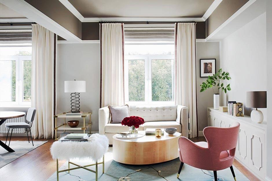 красивый овальный журнальный стол и розовое кресло в гостиной