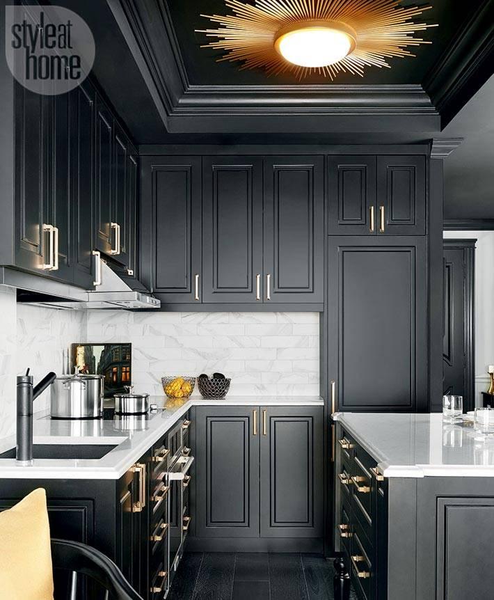 кухня черного цвета с черным потолком и золотой люстрой