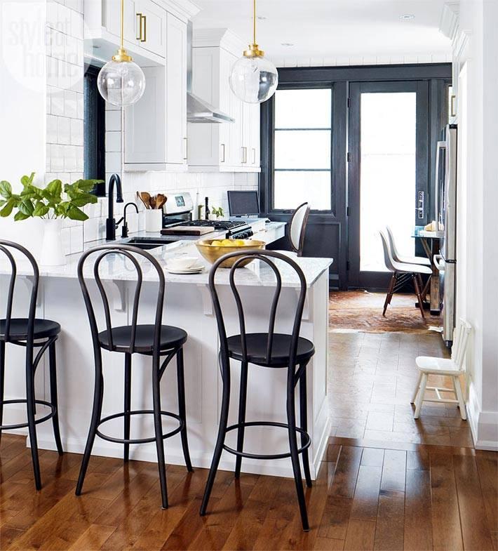 белая кухня с черными стульями и черным окном