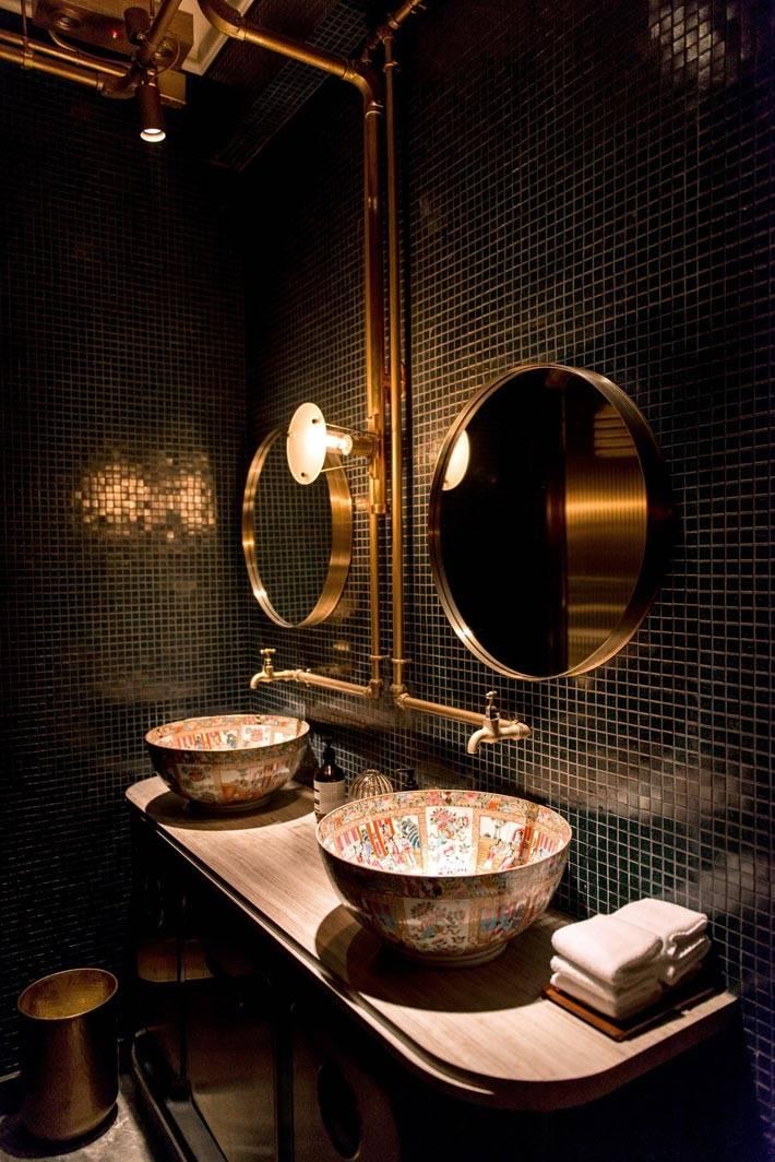 темные стены в ванной комнате и круглые золотые зеркала