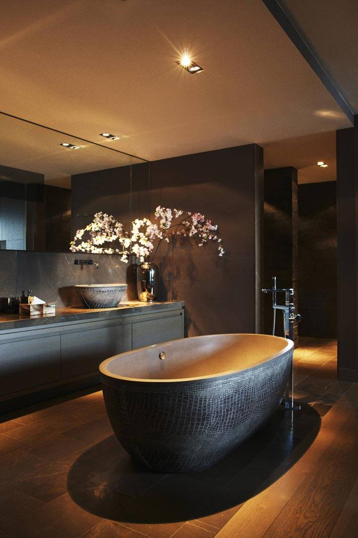 роскошная ванная комната с коричневыми стенами и болльшим зеркалом