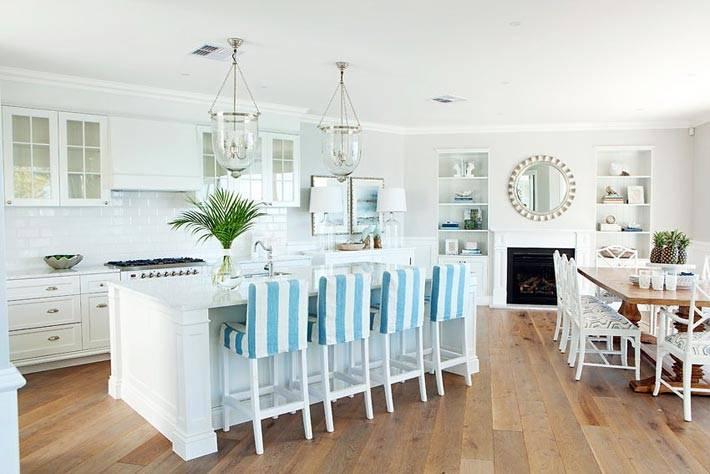 большой интерьер белой кухни с голубыми стульями