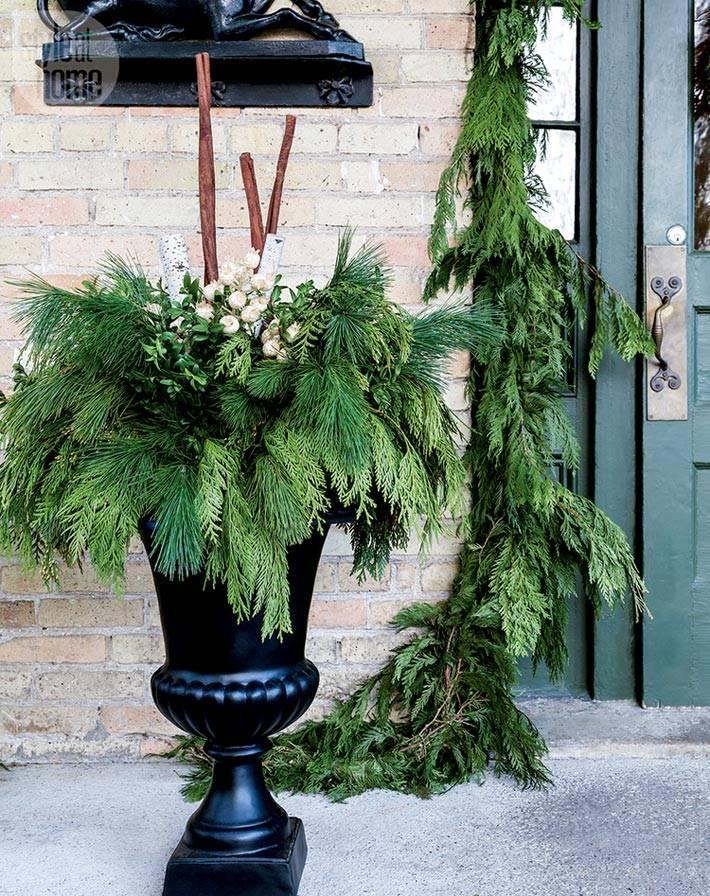 еловые ветки в чугунной вазе при входе в дом