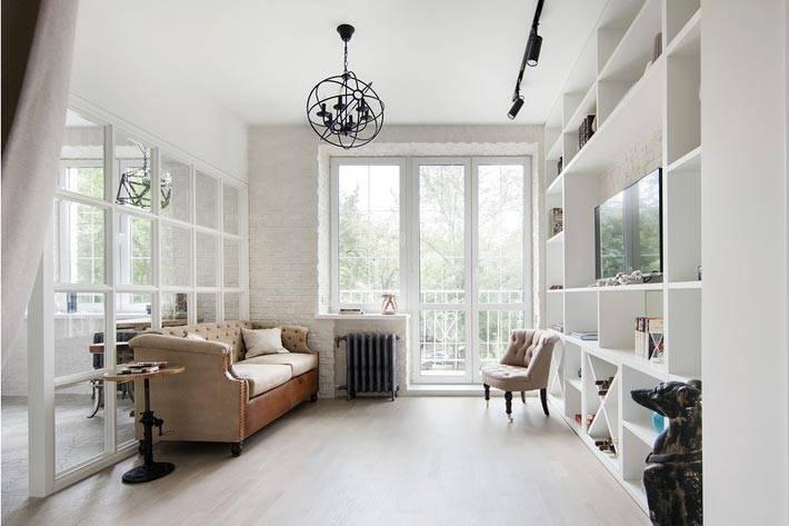 белые кирпичные стены и стеклянная перегородка в квартире-студии