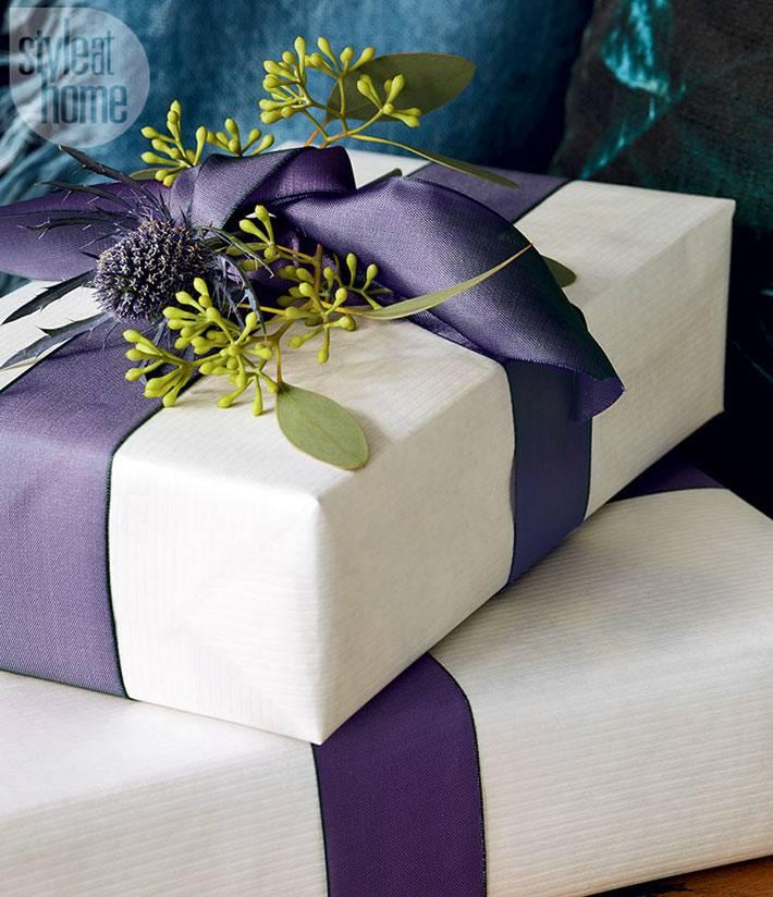 красивая упаковка подарков белой бумагой с фиолетовой лентой