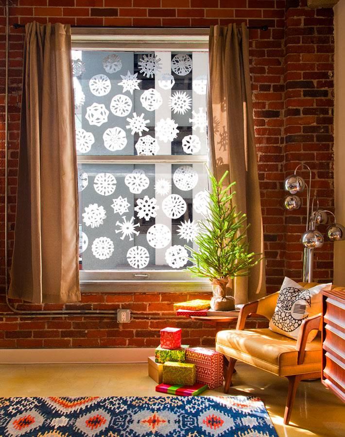 вырезанные снежинки из салфеток клеятся на окна