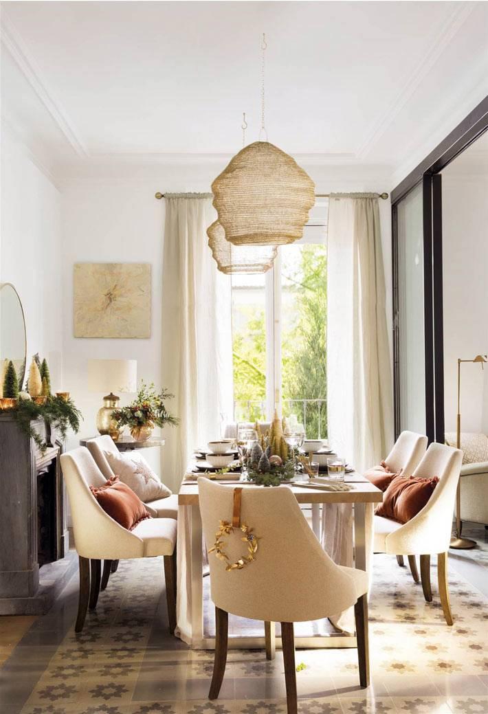 золотые венки на стульях и маленькие елочки на новогоднем столе