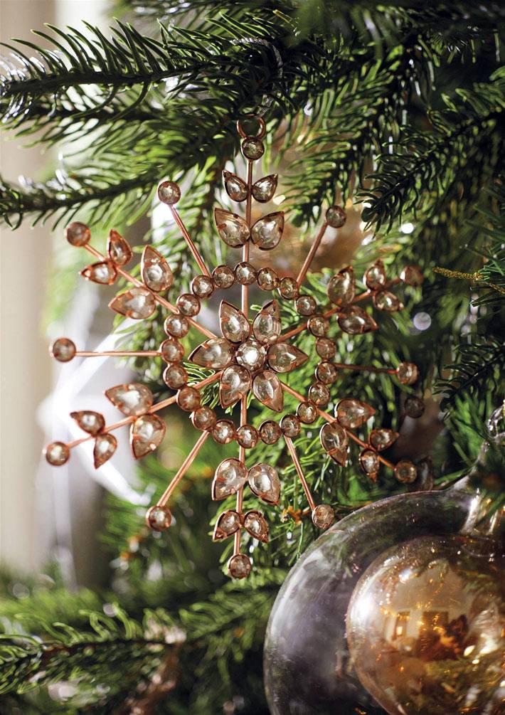 красивая золотистая снежинка на новогодней елке