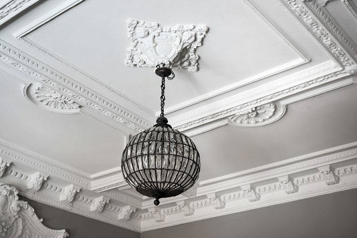 круглая люстра на потолке с лепниной и молдингами