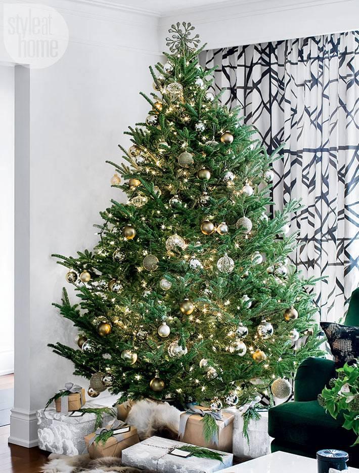 пышная елка красиво украшена игрушками в доме